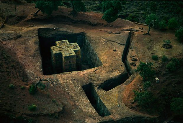 The Church of St. George or Bet Giyorgis in Lalibela, Ethiopia. Its roof is cut into the shape of a square cross, and visitors enter the church via stairs cut down into the volcanic rock. These stairways deepen into trenches that connect to a tunnel that opens to the base of the church and its entrance. Monolithic churches were carved out of the ground to which they are still attached. Eight hundred years ago the Ethiopian King Lalibela had a divine vision to carve a new Jerusalem from…