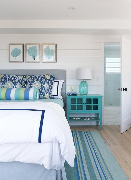Gray and turquoise blue bedroom features a shiplap clad wall lined ...