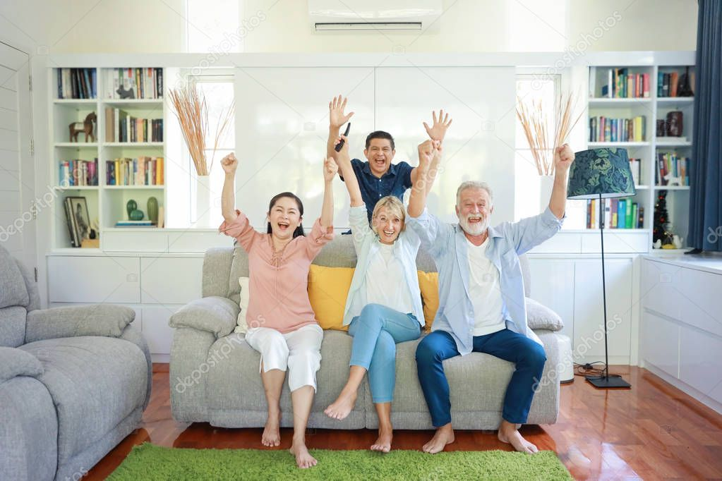 Happy Elder Multiethnic Family Sitting On Grey Sofa In Living Room And They Rais Spon Family Sitting Multiethnic Happy Ad Gray Sofa Smile Face Sit