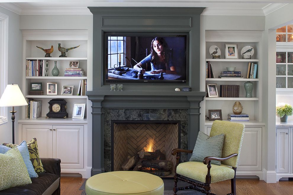 Extraordinary Family Room Wall TV above Fireplace with White Cabinets Bookshelf Decoration and Wood Flooring