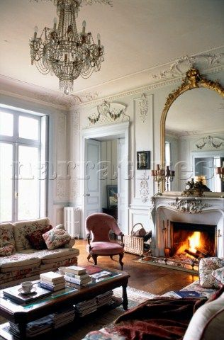 Gilt Framed Mirror Above Fireplace In French Apartment Living Room