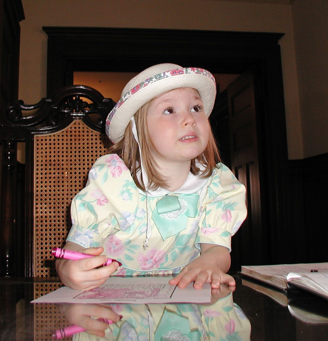 In her Easter bonnet, coloring while waiting for time for church to begin.