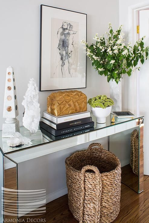 Chic Foyer Features A Woven Basket Tucked Under Mirrored Console Table Topped With Stacked Coffee Books Placed Abstract Sketch
