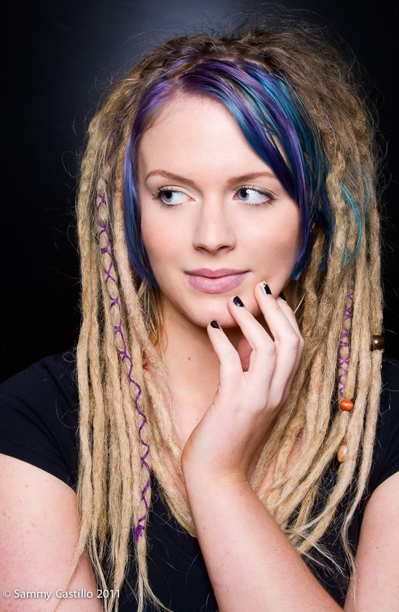 Blonde wrapped dreadlocks with blue and purple bangs.