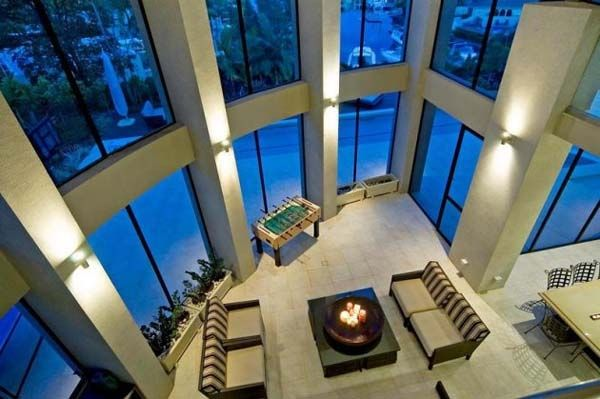 Living room with a very high ceiling and glass walls.