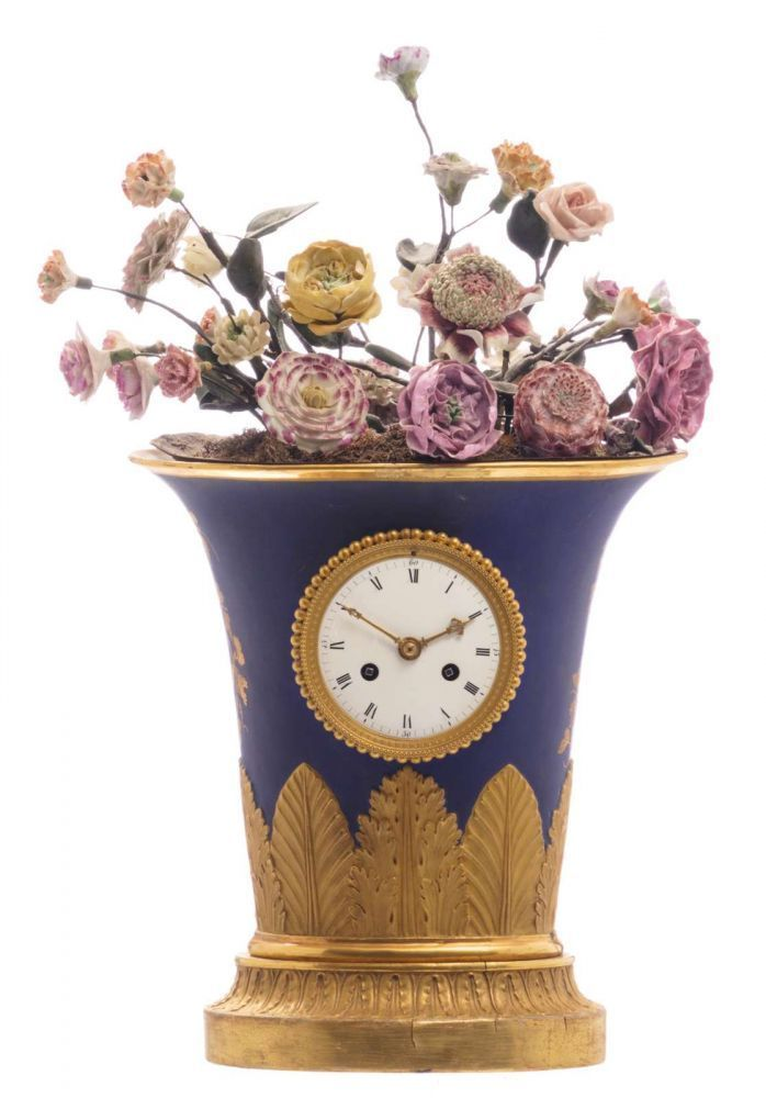 A Neoclassical Probably French Vasiform Porcelain Mantel Clock, On Top A  Tole Jardiniere With Flower