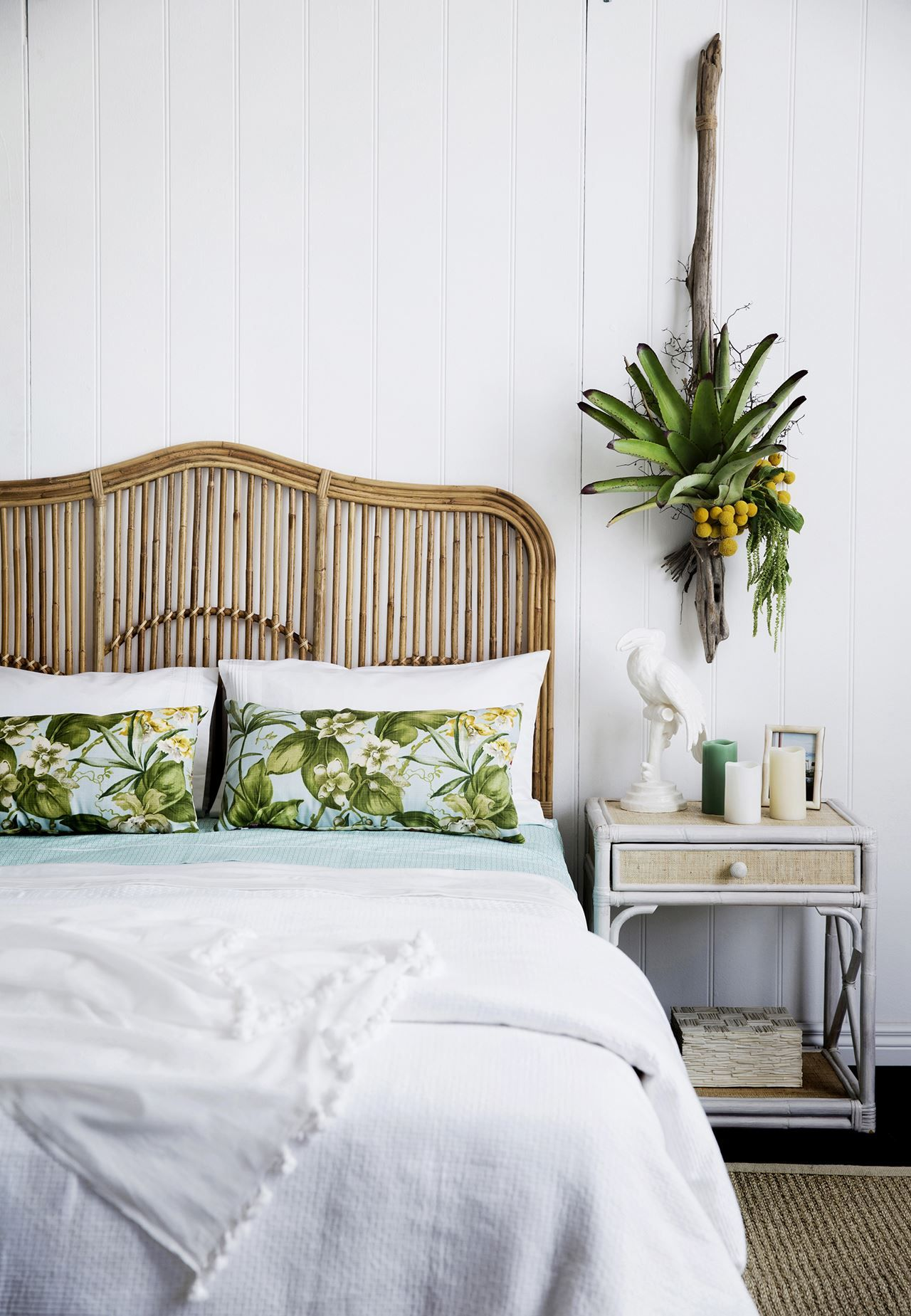 """Panelled white walls and textured bedlinen contribute to a light, airy look. Lincoln Brooks Brookhaven queen-size rattan **bedhead** and Lincoln Brooks La Cruz rattan **side table**from [Naturally Cane](http://www.naturallycane.com.au/