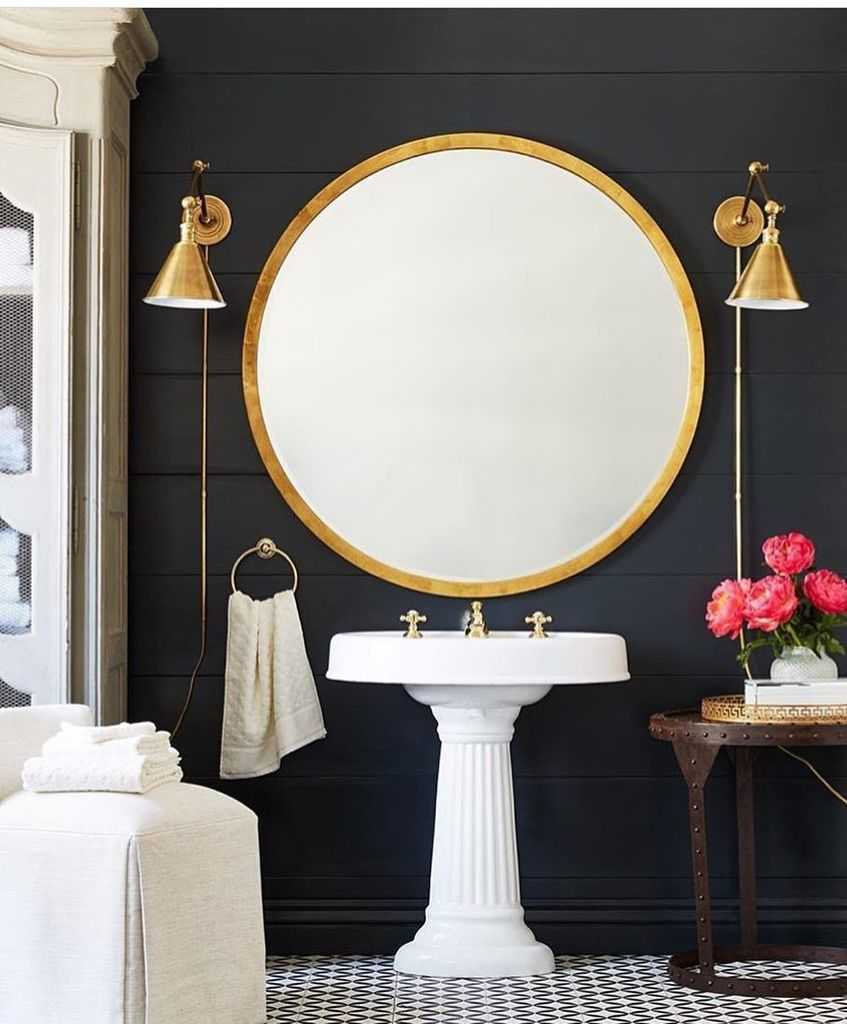 Gorgeous gold round mirror and brass wall sconces in this for Gold bathroom wall lights