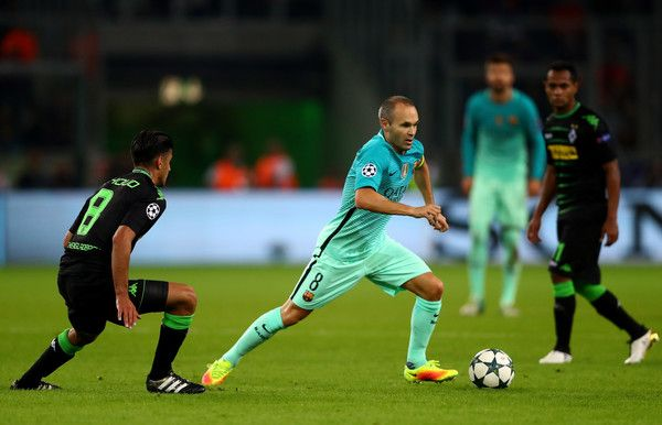 Andres Iniesta of Barcelona runs with the ball under pressure from Mahmoud Dahoud of Borussia Moenchengladbach  during the UEFA Champions League group C match between VfL Borussia Moenchengladbach and FC Barcelona at Borussia-Park on September 28, 2016 in Moenchengladbach, North Rhine-Westphalia.