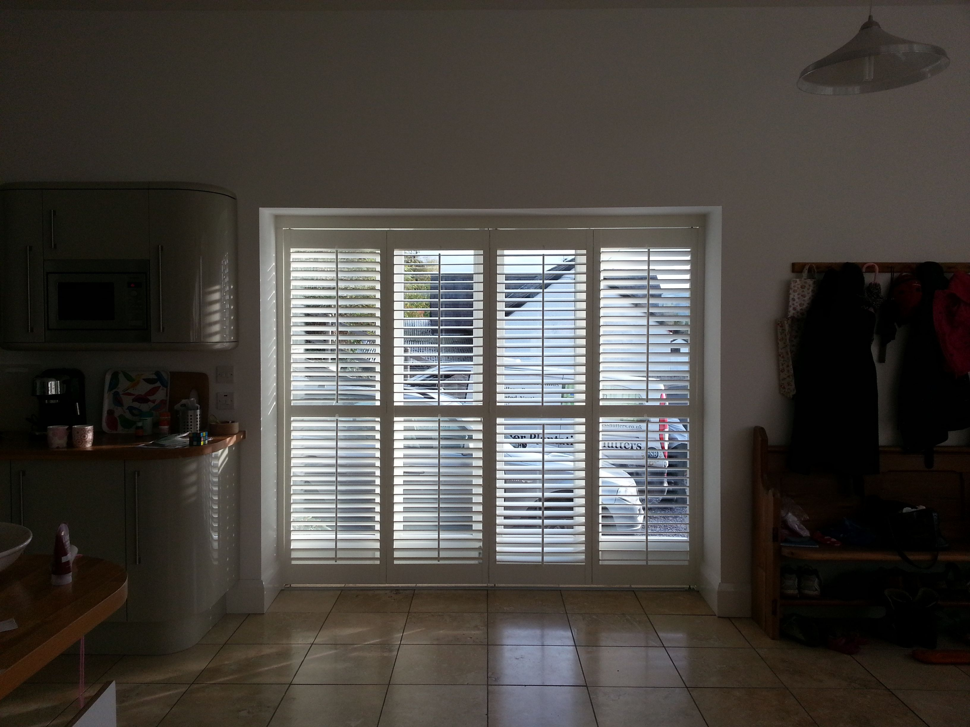 Wooden plantation shutters fitted to patio doors on a track system