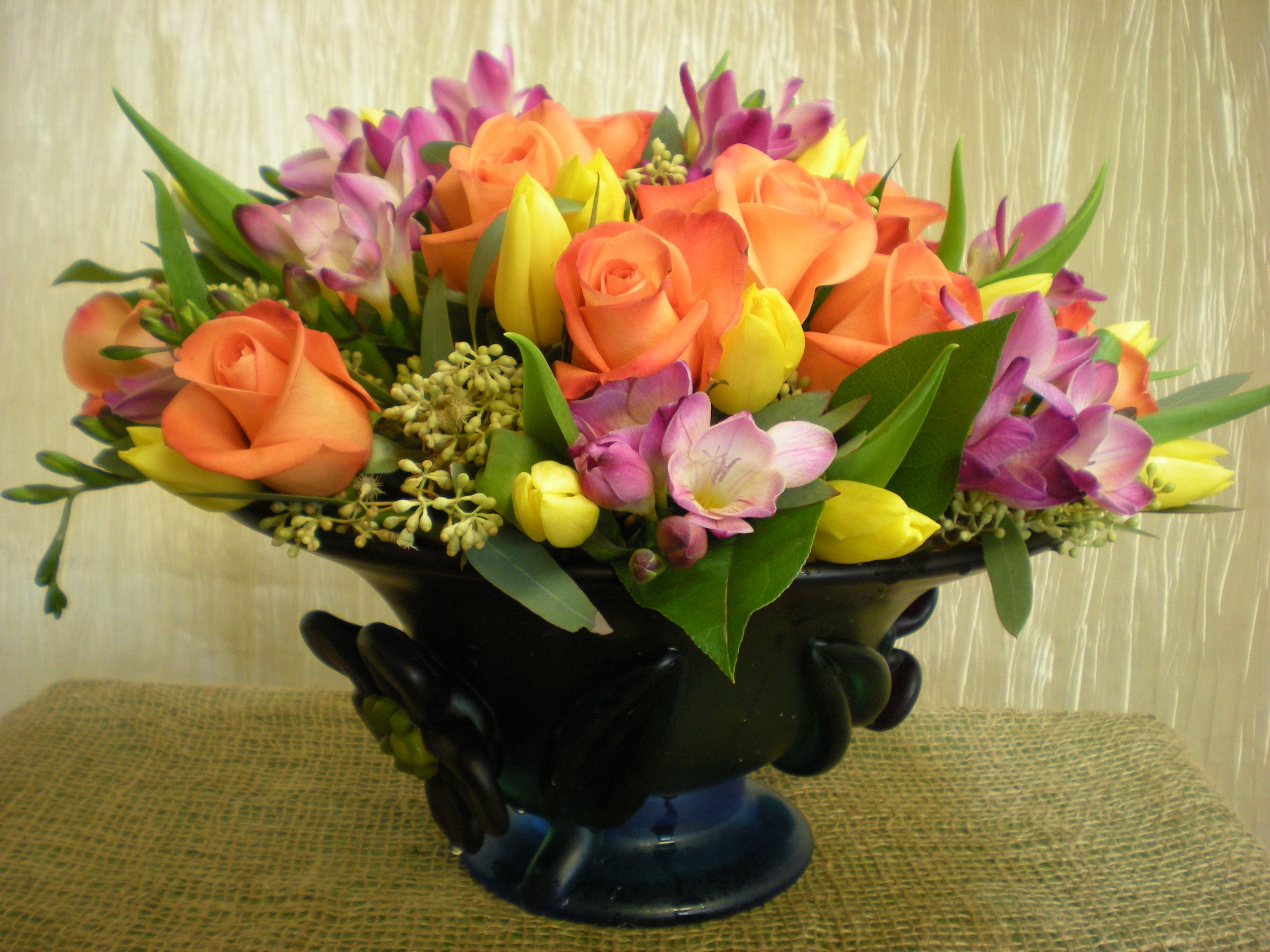low & lush for springtime orange roses yellow tulips purple