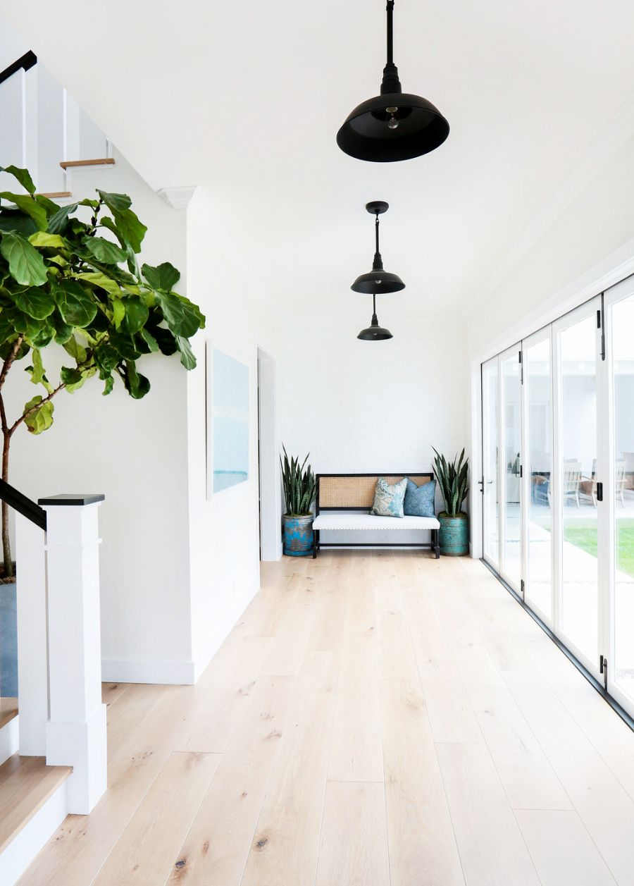 White walls light hardwood floors black hanging light fixtures white bench and blue throw pillows