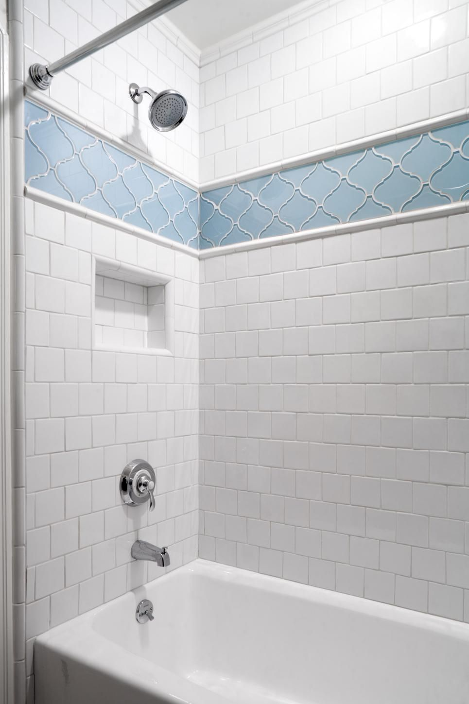 This traditional white tile shower features a blue patterned accent ...