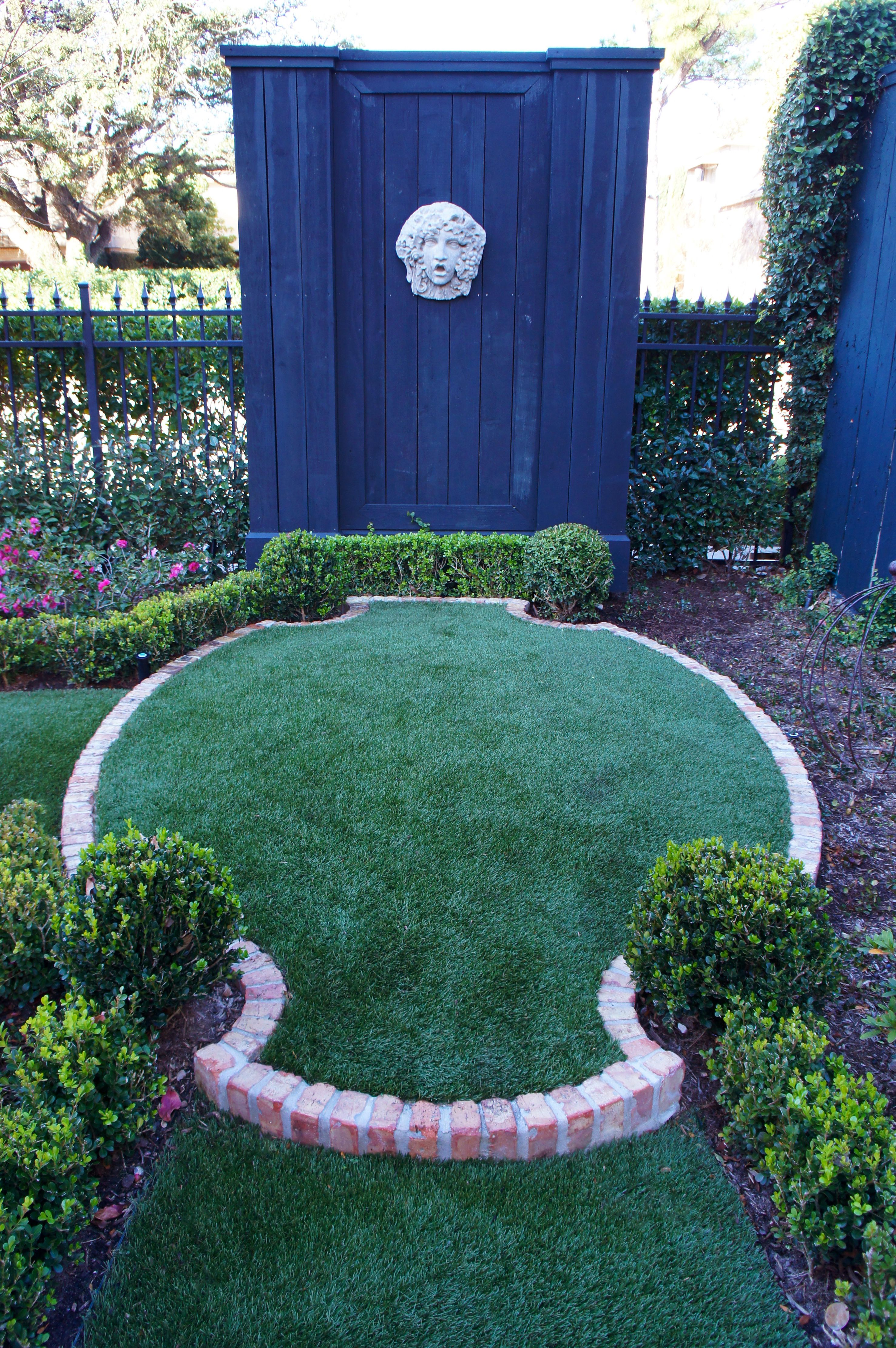 Boasts Clic Finials And Garden Decor Synthetic Lawn Bordered With Red Brick Accented By Boxwood Hedges