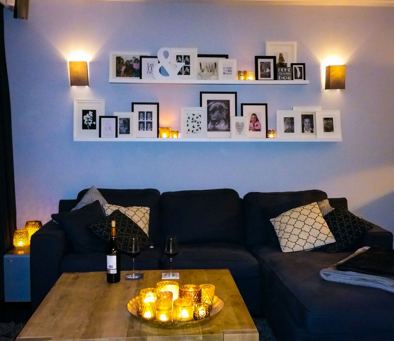 Witte wandplankjes ikea aan de muur in de woonkamer met fotolijstjes zwart wit met foto 39 s en - Zwarte muur in de woonkamer ...