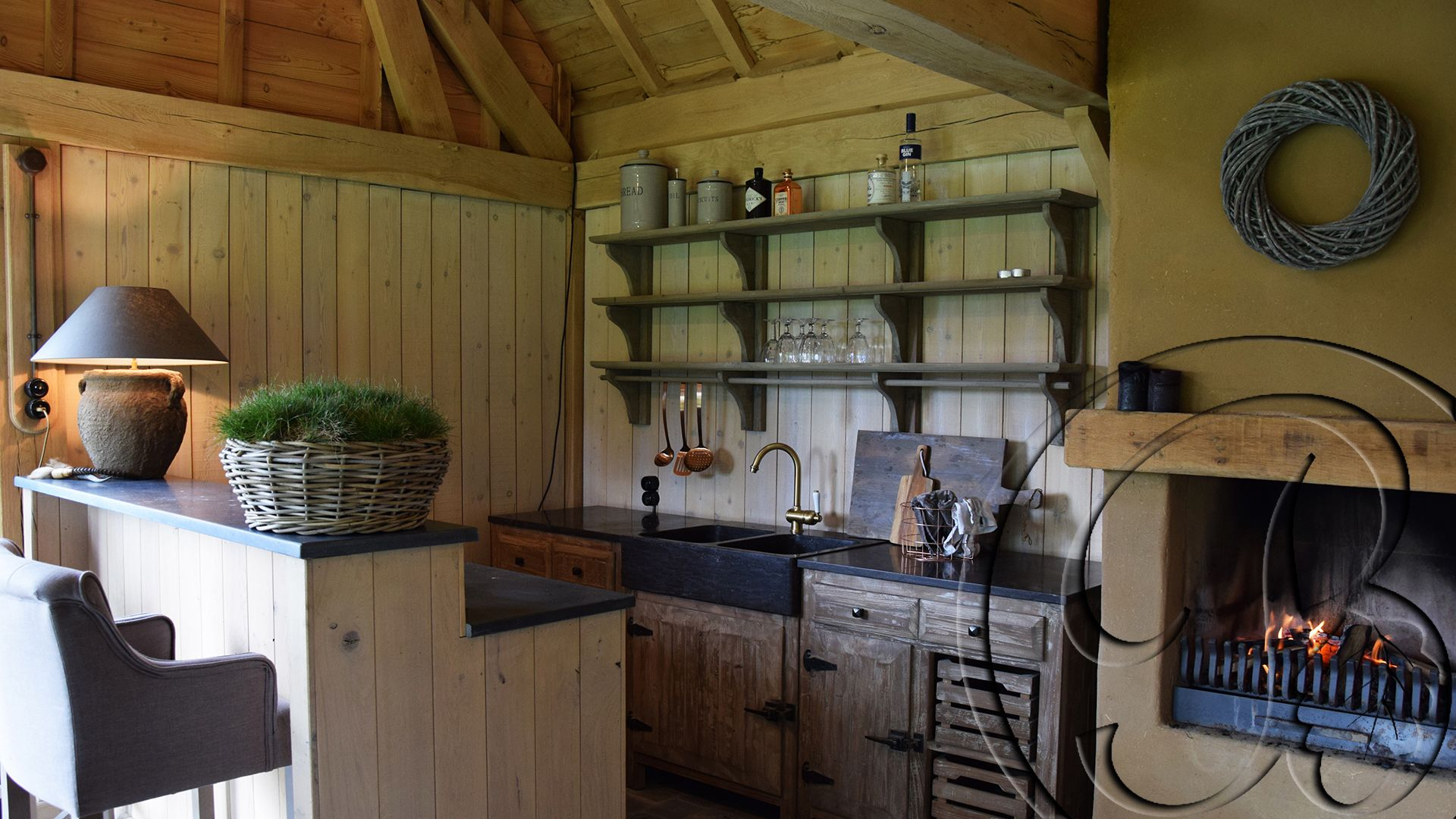 Poolhouse keuken met gekaleide open haard in een houten bijgebouw