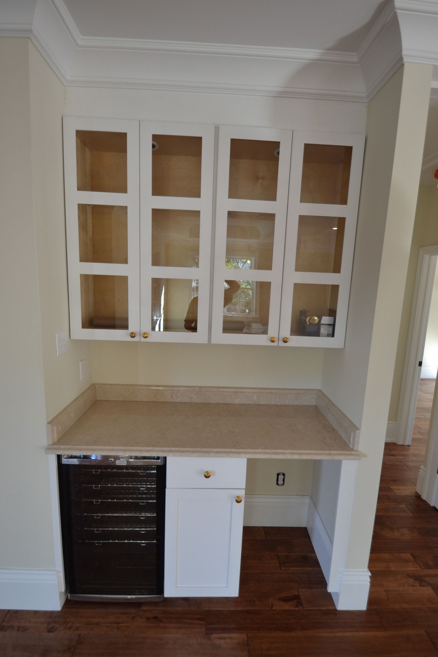 Custom designed and built cabinets, crema marfil marble countertop, glass front wall cabinets, under-counter wine fridge and space/plumbing for under-counter ice maker