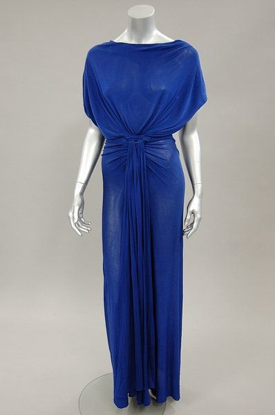 Madame Grès couture sapphire blue draped jersey `Goddess' gown, circa 1970, black on white 1 Rue de la Paix label, with cowl neck, drapes of fabric curve forwards at the waist and cascade into drapes held in a band at the centre front, naked triangular lower back section. Front