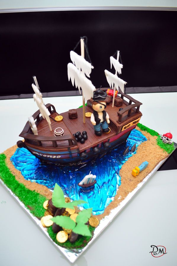 """Pirate ship cake which is a 14"""" x 4.5"""" chocolate cake.  Water is a piping gel tinted with blue icing color; sand is crushed digestive biscuits and grass is dessicated coconut colored with green food color.    Thanks to pt4pastries (flickr) for the ship design and to our very own cc member, Karen Sue, for the helpful tips and tutorial on making 3D ship :)"""