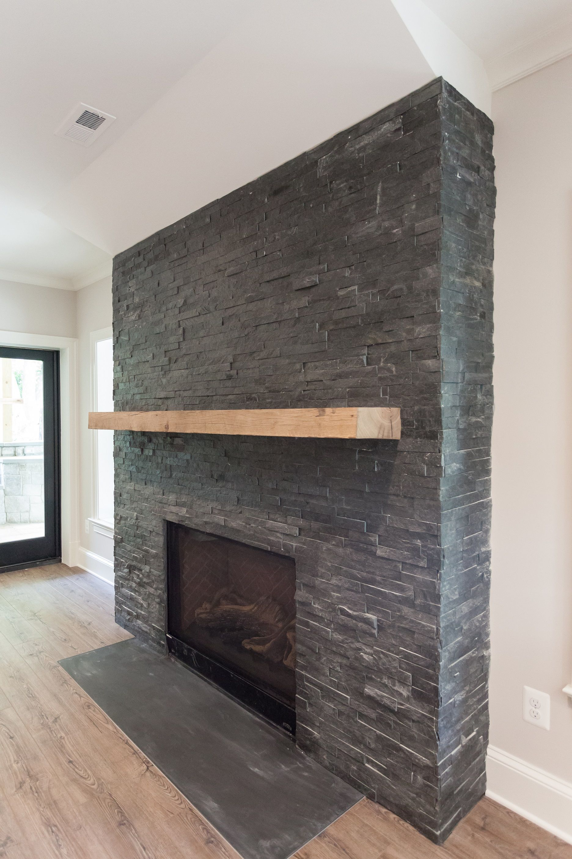 Black Stacked Stone Fireplace With Reclaimed Natural Wood Mantel
