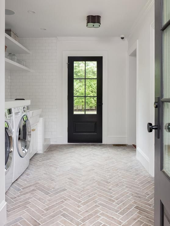 Basil Flush Mount illuminates a modern farmhouse white laundry room completed with faded red brick herringbone pavers.