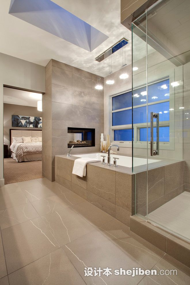 This Ultra Modern En Suite Holds A Grey Tile Covered Bathroom In Which A  Glass Shower Enclosure, Large Window Side Soaking Tub, And Pass Through  Fireplace ...