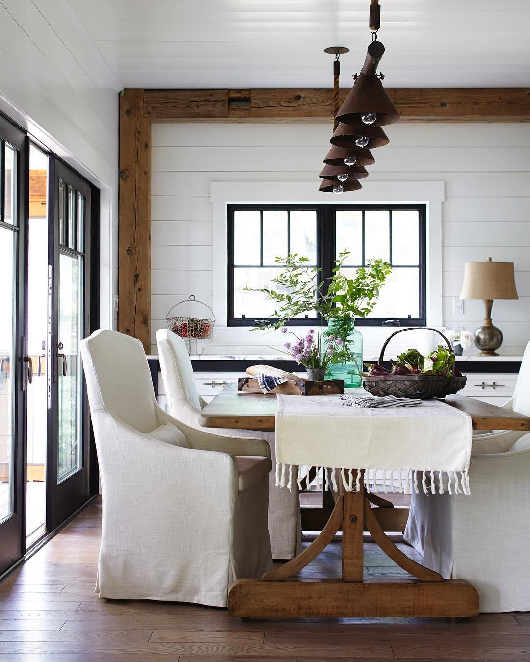 Rustic Farmhouse Style Dining Room With Black Windows, Slipcovered Chairs,  Rustic Beams And Shiplap.