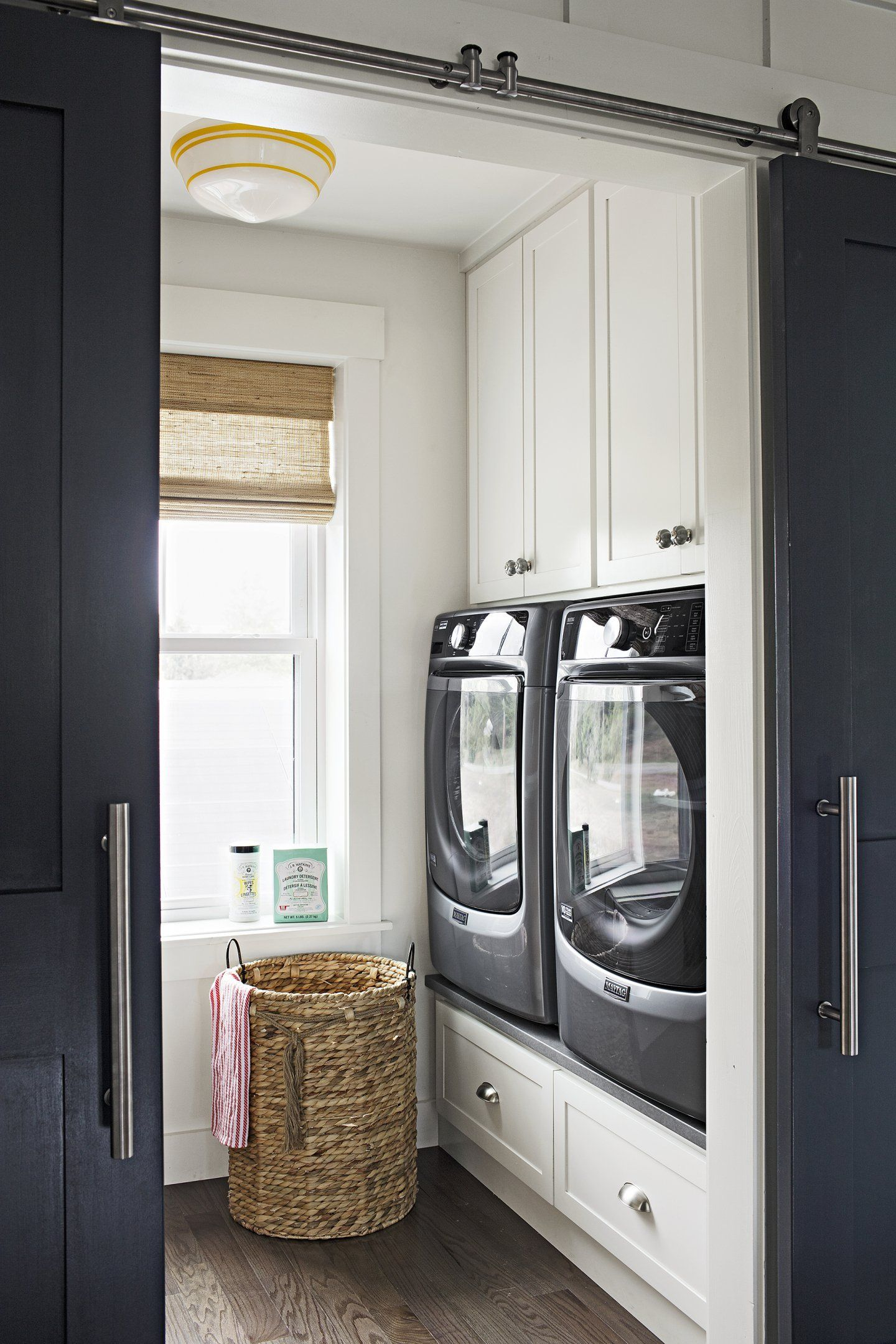 The compact laundry room is super-functional thanks to built-ins surrounding the washer and dryer, and another wall of cabinets with a countertop for folding clothes on the opposite side of the room. Redi-Prime Shaker-style 8782 barn doors; simpsondoor.com. Schoolhouse ceiling fixture by barnlightelectric.com. Wendy Bellissimo woven shade by smithnoble.com