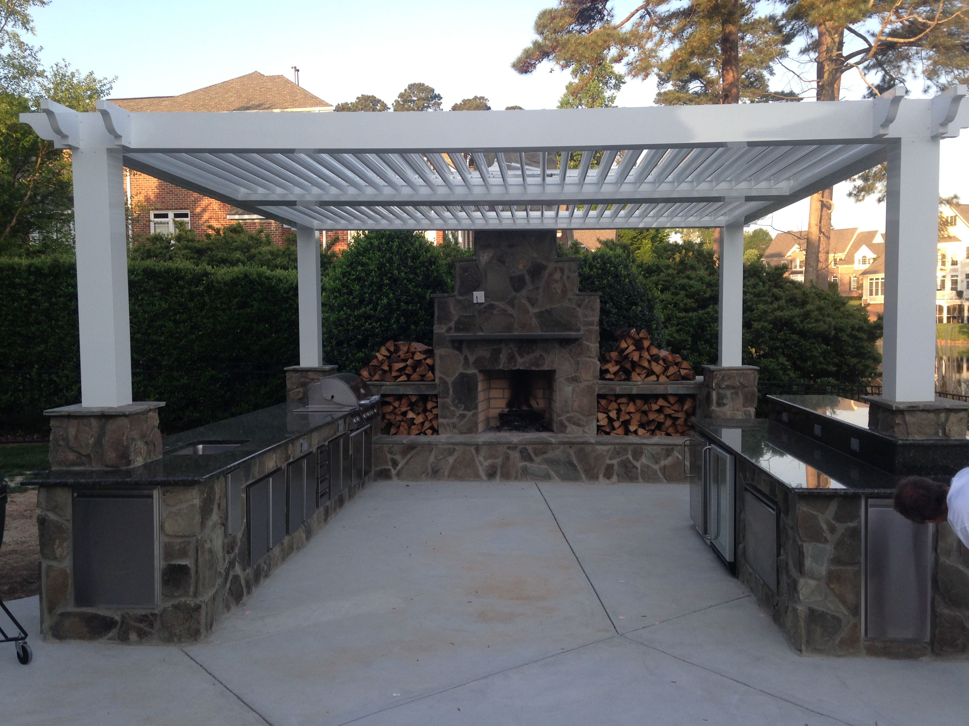 customized stone outdoor kitchen with pergola and fireplace