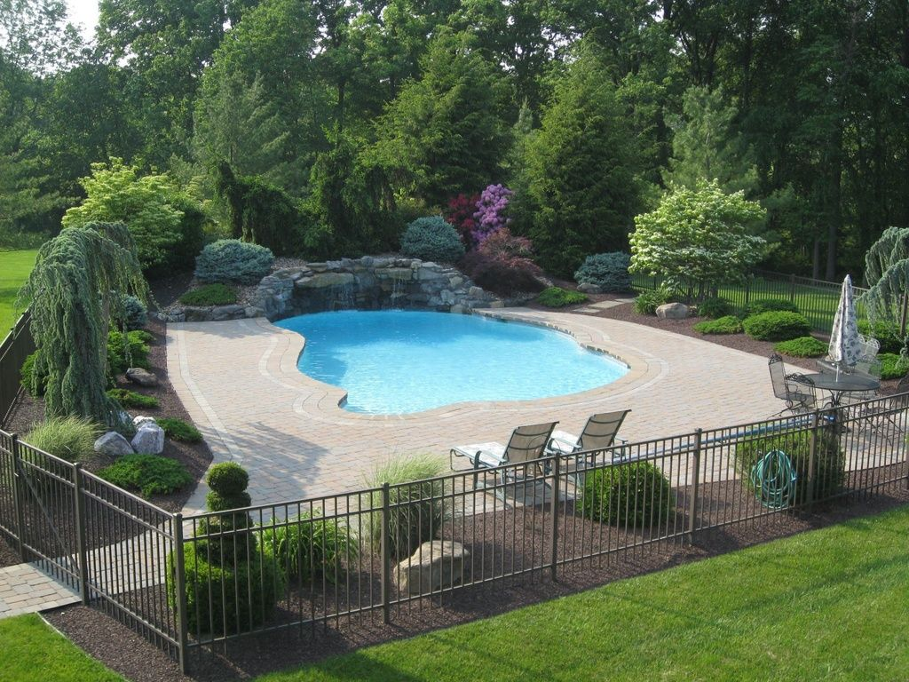 Traditional swimming pool with fence exterior brick for Backyard landscaping pictures