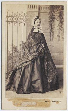 DigitaltMuseum - Kabinettsporträtt. Porträtt i helfigur av stående kvinna iklädd vid, blank kjol. Över axlarna bär hon en paiselymönstrad sjal och på huvudet en mössa med breda band knutna i rosett under hakan.