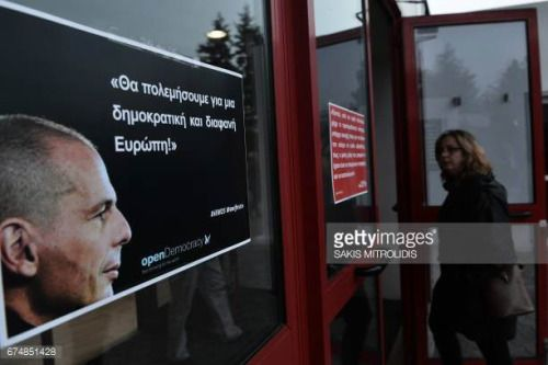 04-29 A woman looks at a banner with the image of former Greek... #biberachanderriss: 04-29 A woman looks at a banner… #biberachanderriss
