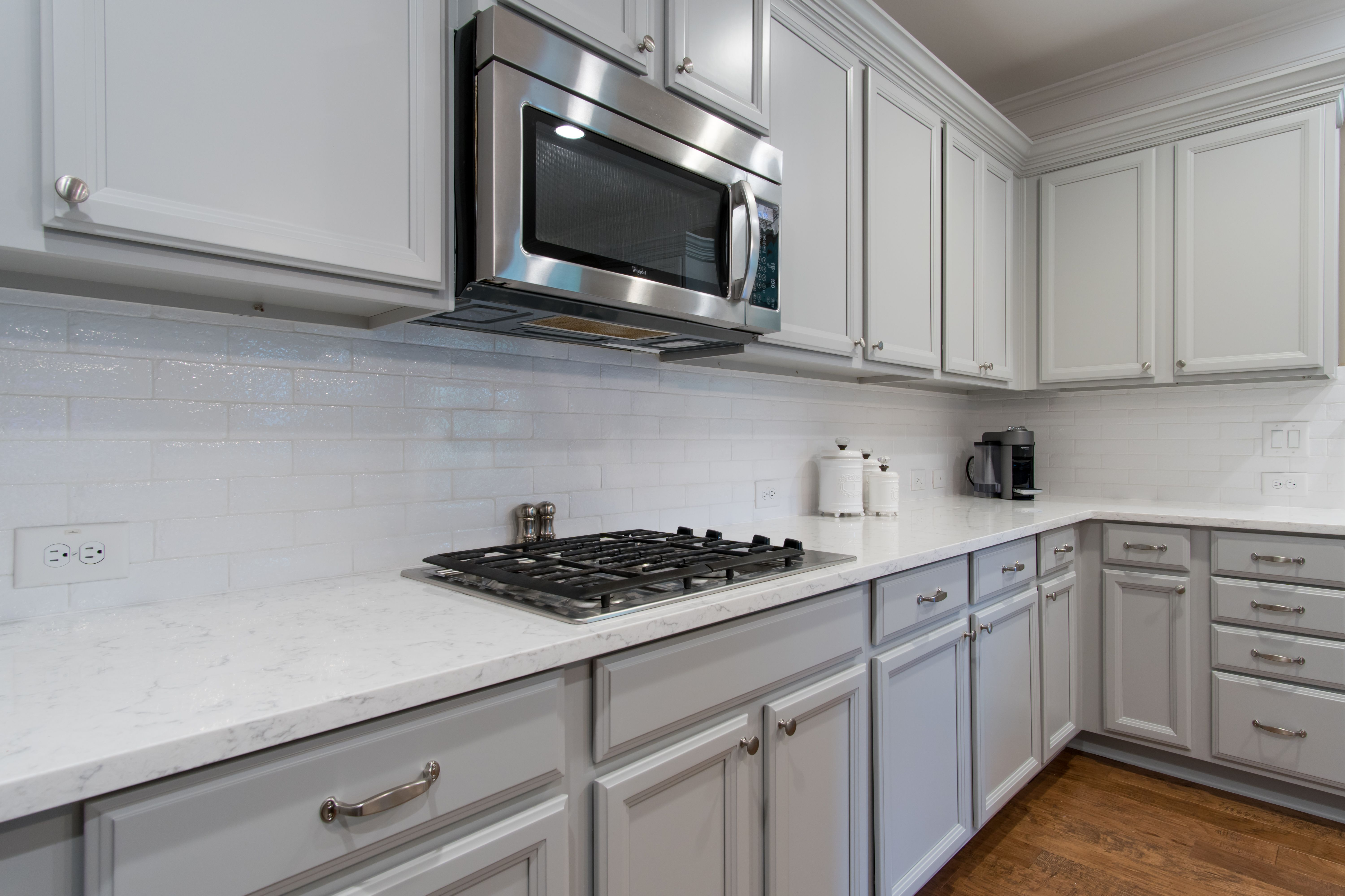 Refinished Cabinets In A Light Gray With New Silver Hardware Quartz Countertops Stainless Steel Appliances And Kitchen Design Refinishing Cabinets Countertops