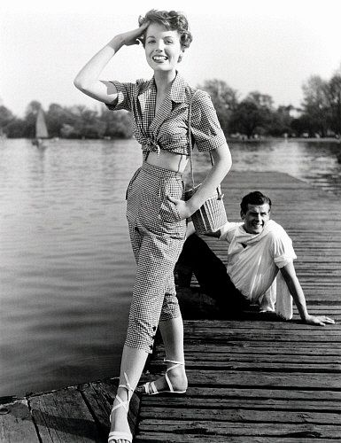 Model Pat Goddard in Malcom Brown gingham blouse and jeans with Roger Moore, photo John French. London, UK, 1952