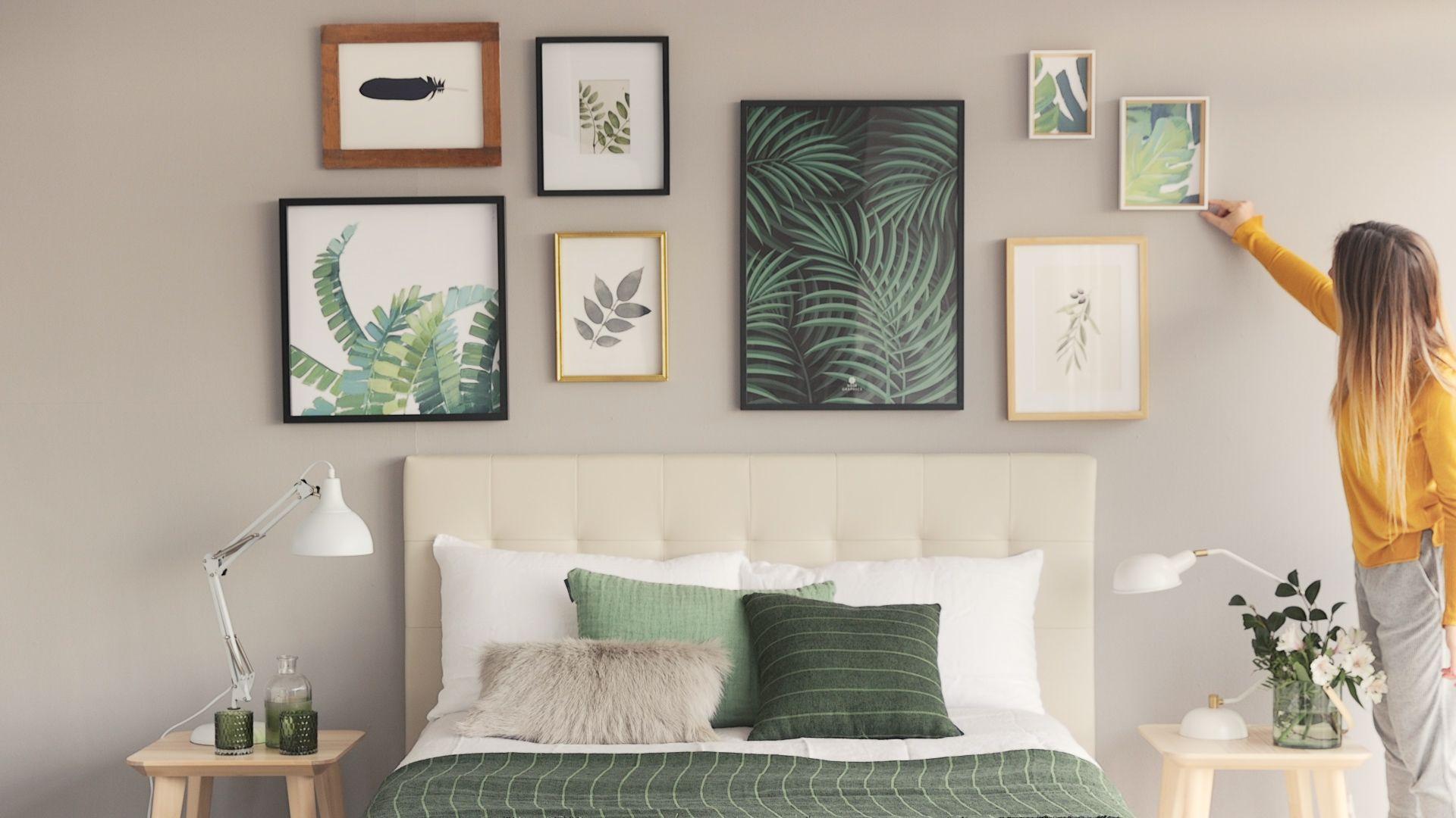 Chica colocando cuadros con dise±os de plantas y hojas en la pared