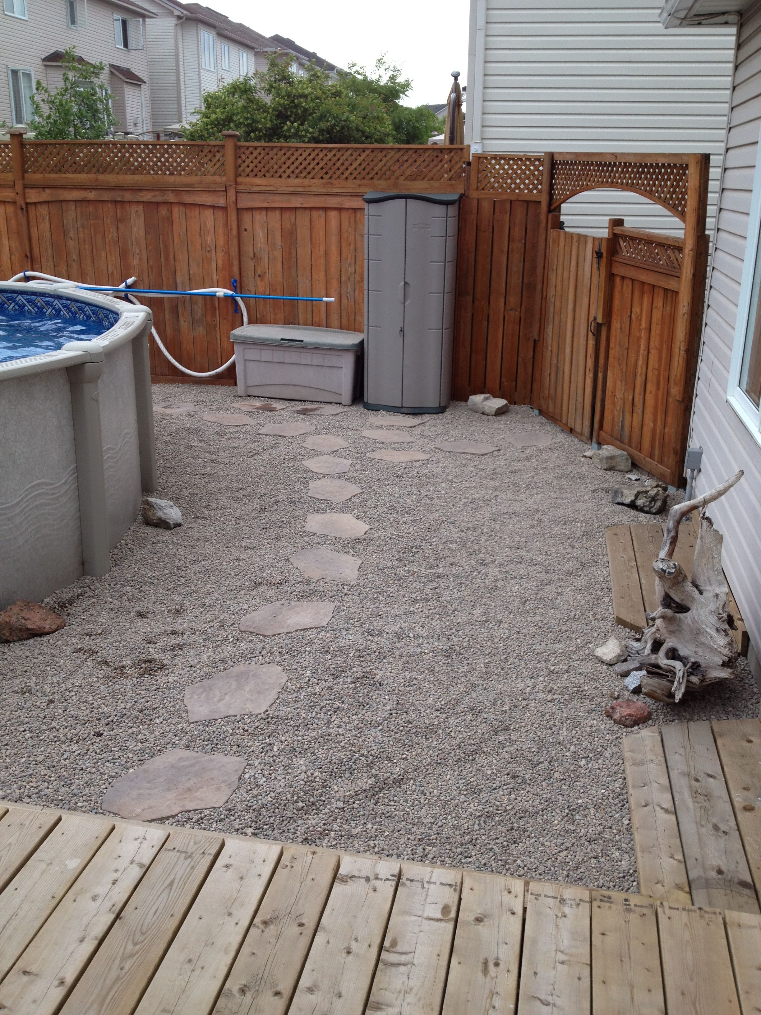 Landscaping around our 18 39 above ground pool riverstone rock for Above ground pool storage ideas