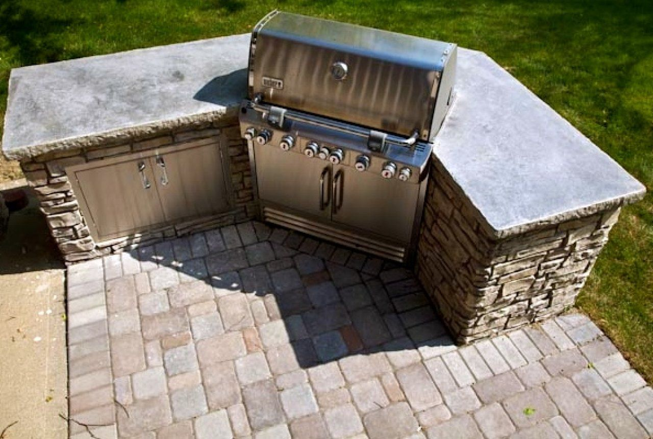 We created this project literally from the ground up. We started by installing a concrete paver patio and anchoring it with the grill island featuring vertical stamped concrete. The top is concrete with a split stone edge.