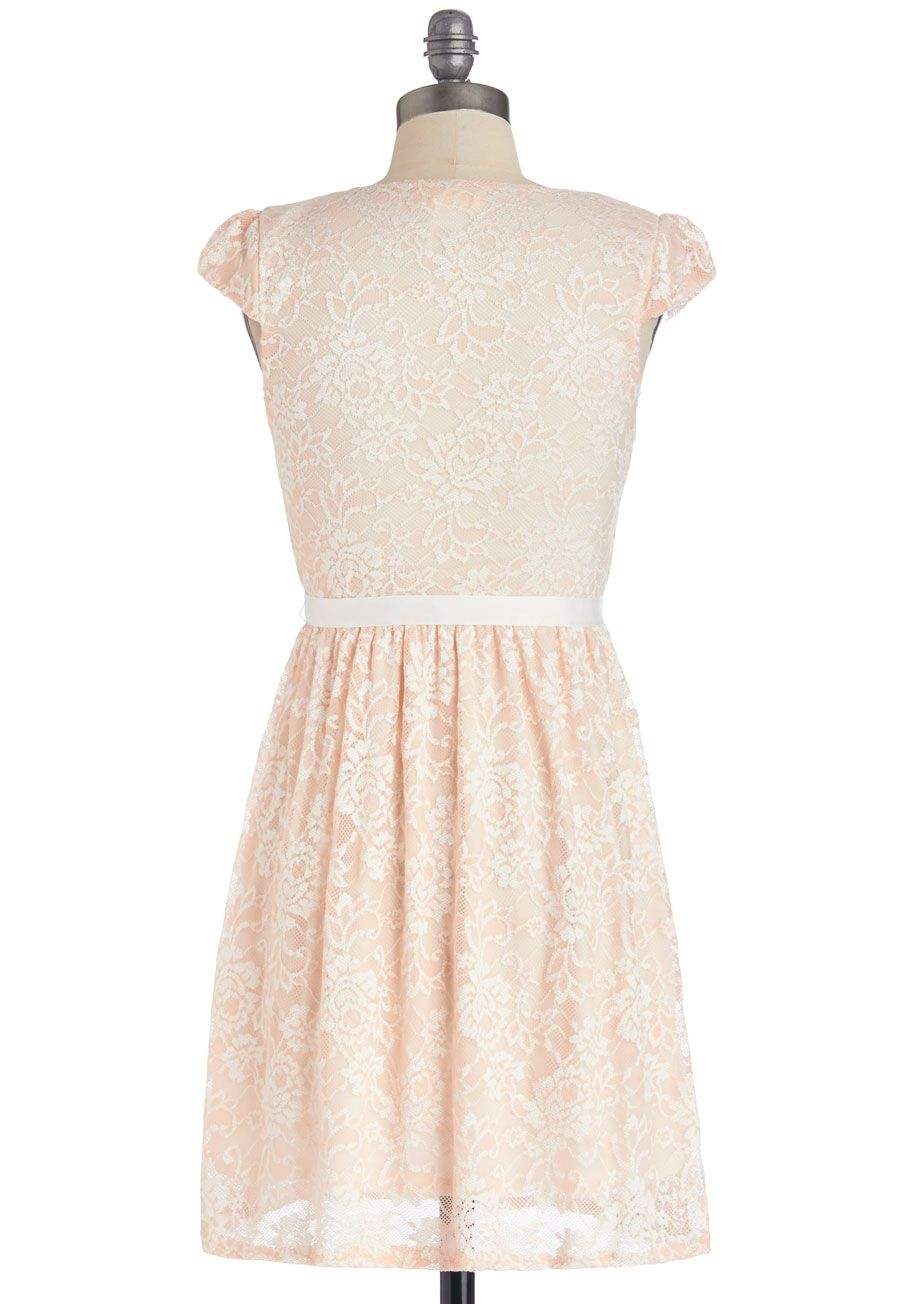 Poised in peach dress as if the peach lace curtained over this