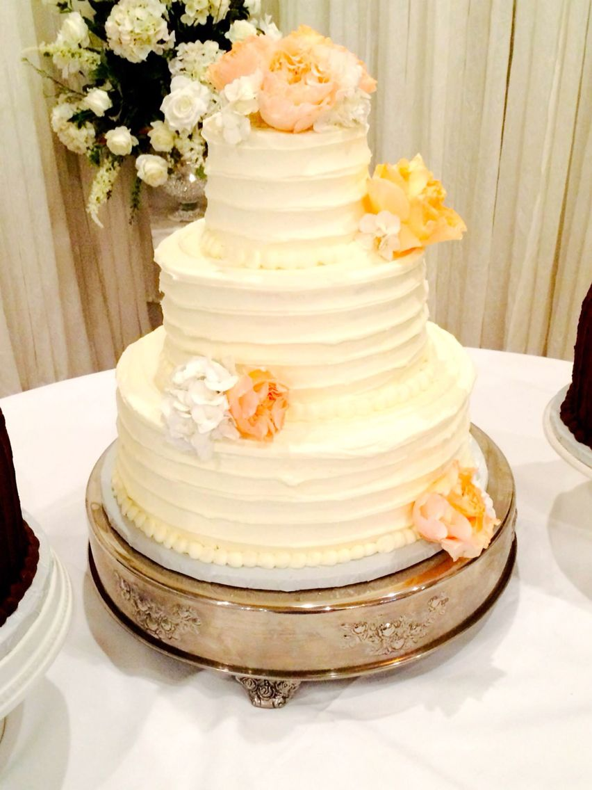 Three tiered horizontal lined textured buttercream wedding cake with ...