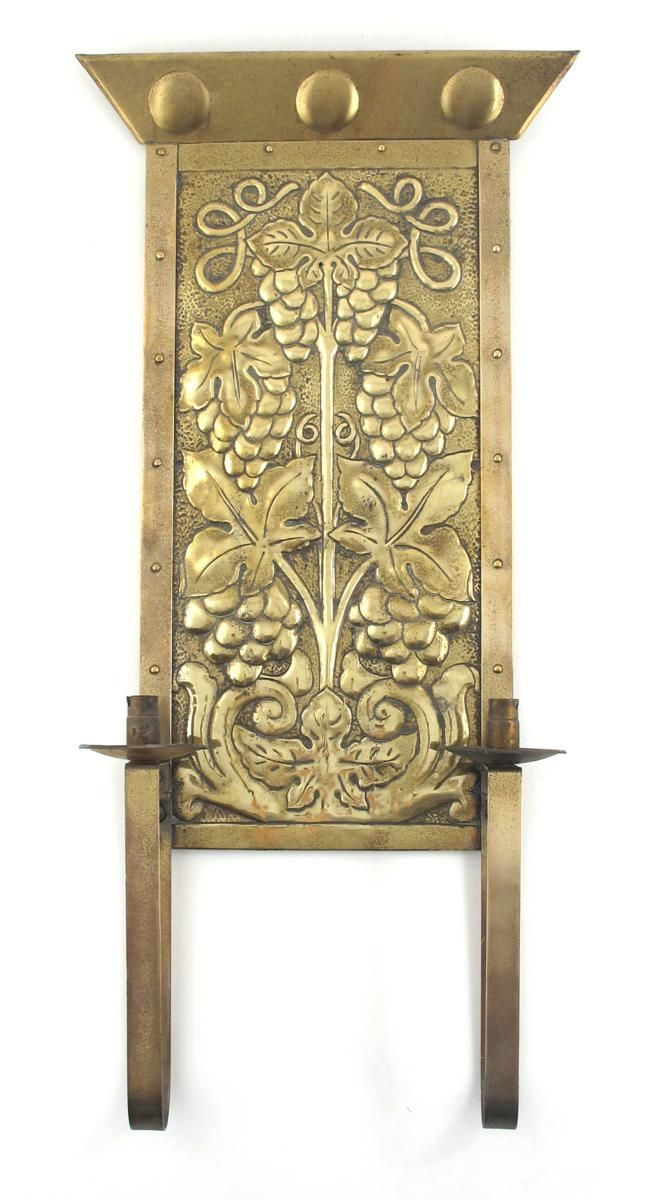 An Arts and Crafts brass wall sconce, probably Scottish, the back ...