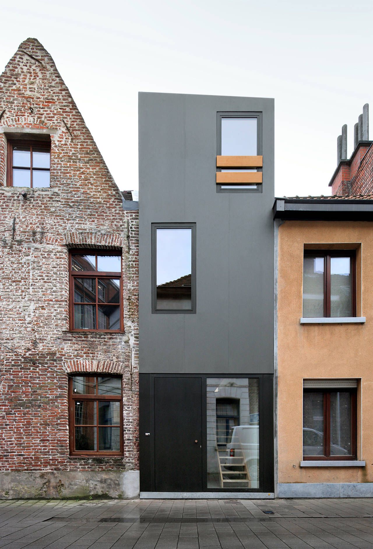 a narrow house squeezed in between two adjacent buildings