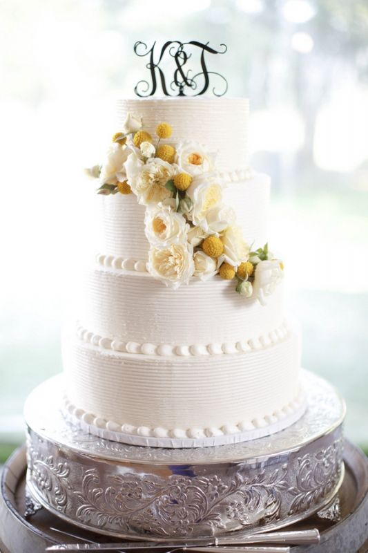 White wedding cake with cascading yellow flowers.   photo by K Stone Photography
