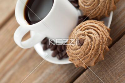 tilt image of coffee cup and cookie with beans. - Close-up tilt shot of coffee cup with cookies and coffee beans on wooden plank.