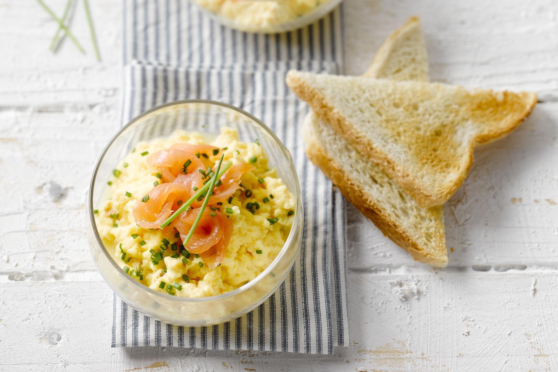 eigerecht - gerookte zalm, eieren, ... - Klop de eieren los met de room. Breng op smaak met peper en zout. Roer er de helft van de bieslook onder.
