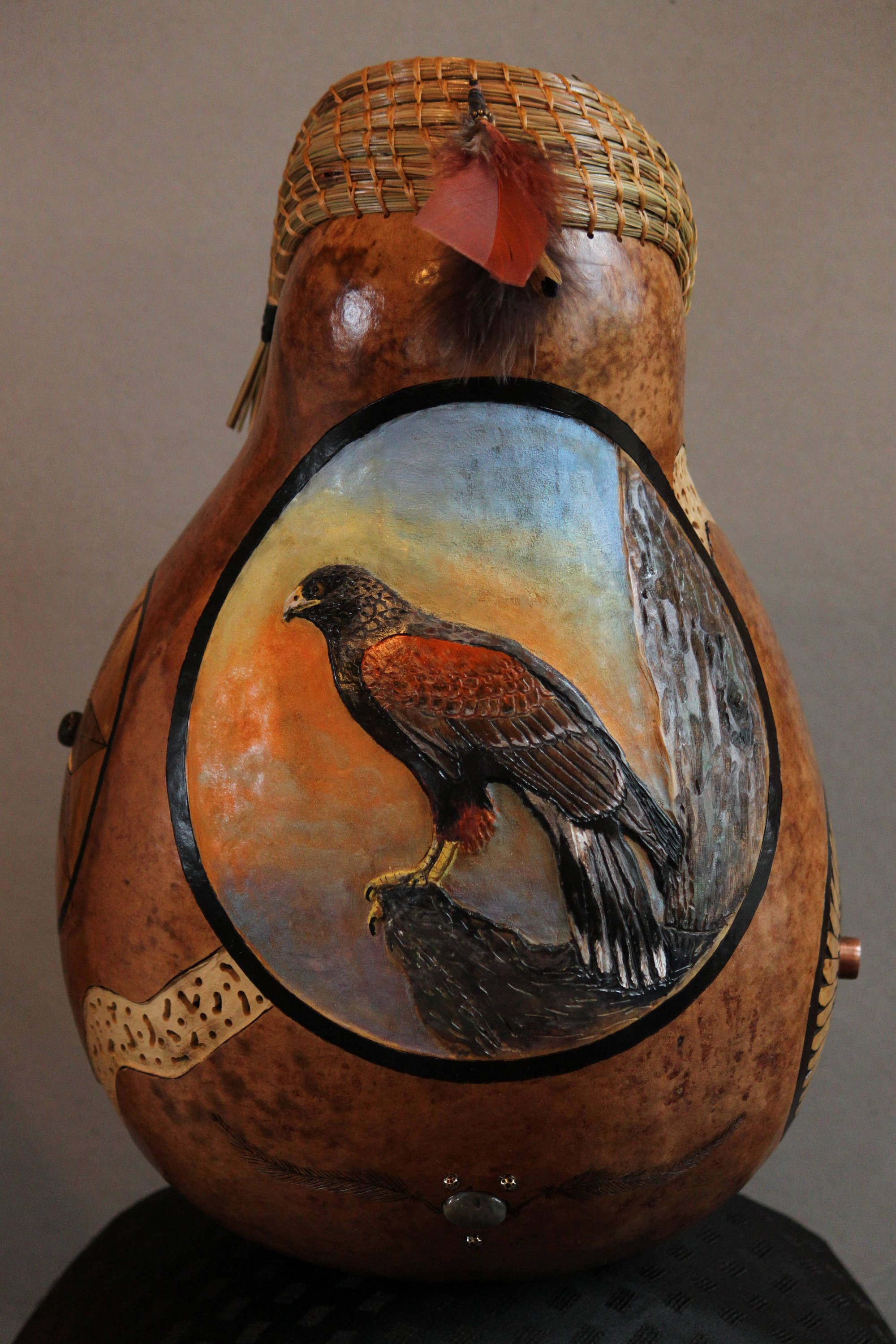 This is a large gourd with a relief carved and painted harriss