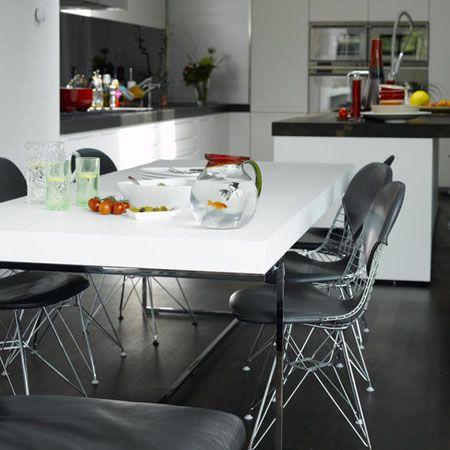 cocina blanca con suelo, pared y encimera en negro mesa comedor en