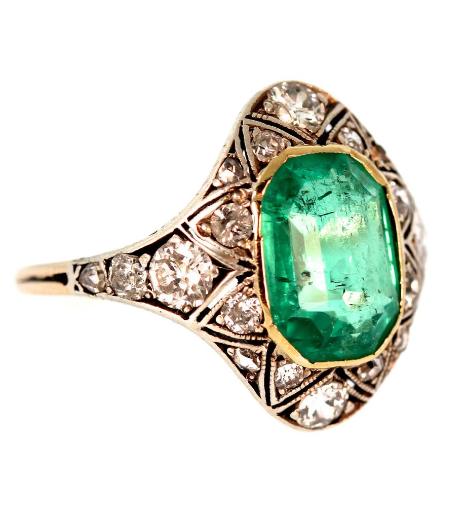 This gorgeous silver topped gold ring was handmade in 1910 and features a 2.75 carat emerald cut Emerald. Accenting the Emerald are 21 Old European Cut, Rose Cut and Single Cut diamonds weighing 0.73