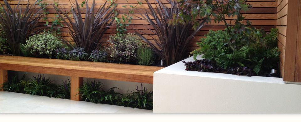 contemporary garden design with hardwood bench  horizontal baton trellis and feature raised