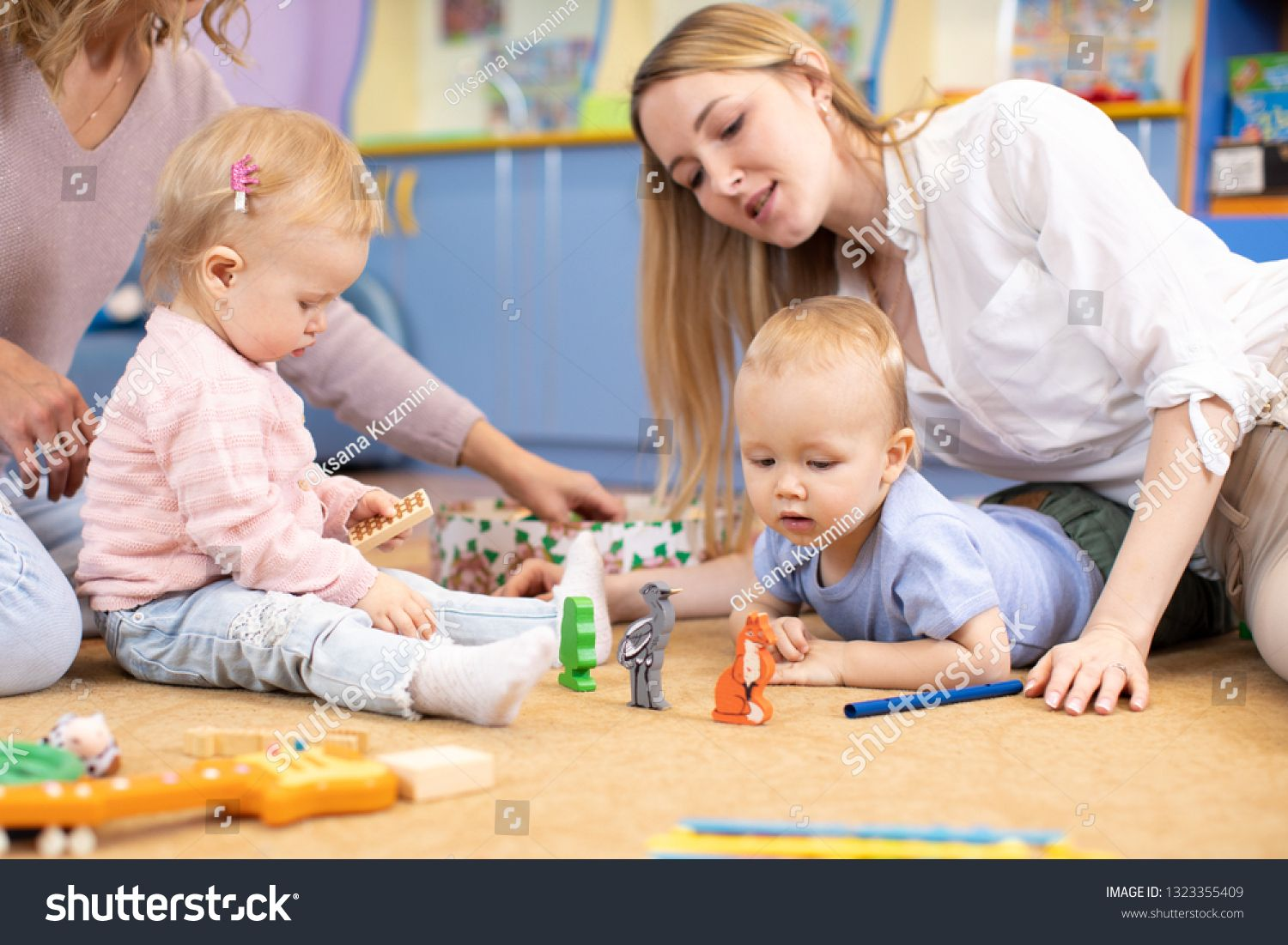 Nursery Babies With Moms Or Teachers Playing With Wooden