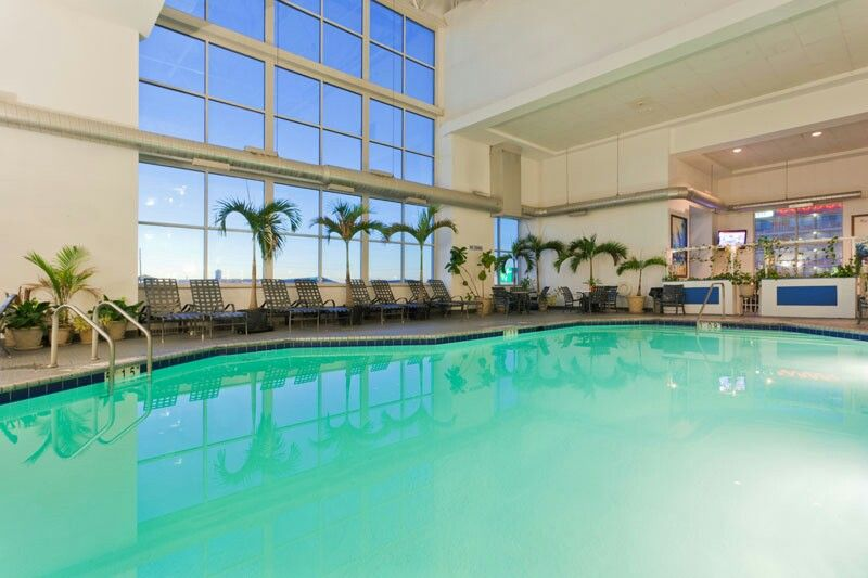 The Indoor Pool And Surrounded By Palms In A Four Story Atrium In The Holiday Inn Hotel And Suites Here In Ocean Ocean City Maryland Ocean City Maryland Hotels